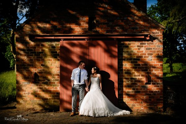 Bride and groom standing in front of old workshop with dappled light