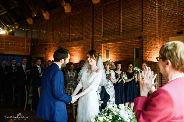 Bride and groom smiling during wedding ceremony at Avoncroft