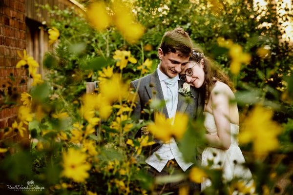 Bride and groom cuddled up surrounded by yellow flowers