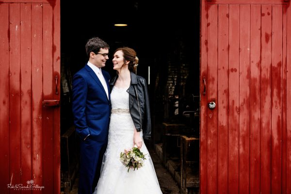 Bride and groom standing between red workshop doors at Avoncroft Museum