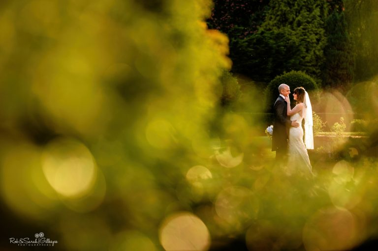 Bride and groom in gardens at Coombe Abbey surrounded by greenery
