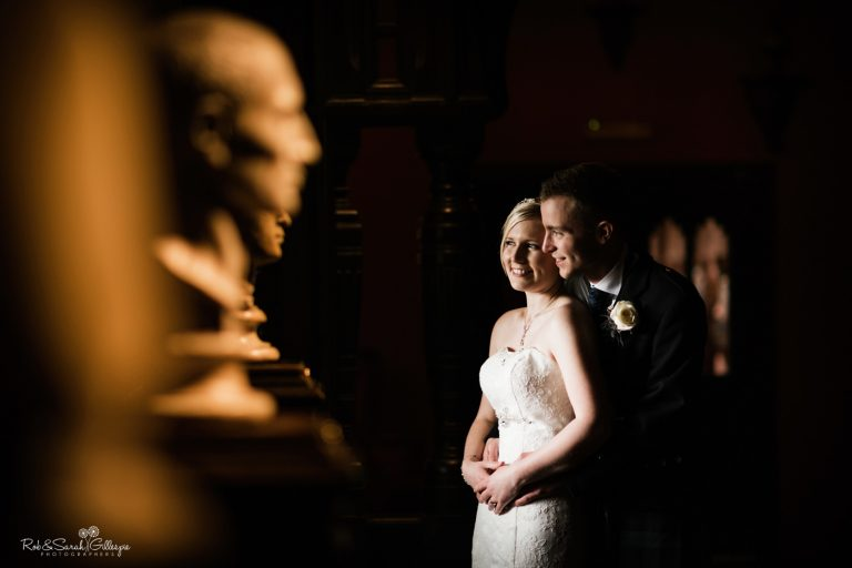 Newly married couple cuddled in dark corridor at Coombe Abbey with statue busts