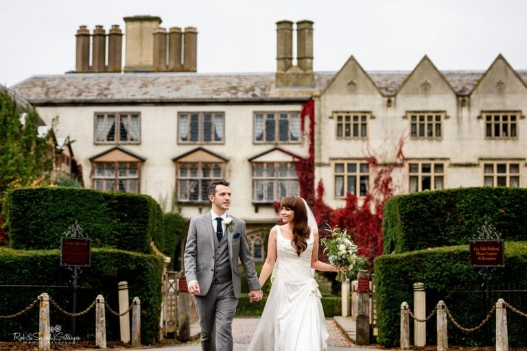 Bride and groom walk hand in hand in front of Coombe Abbey