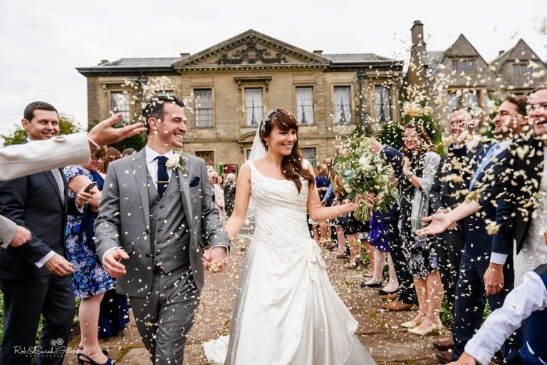 Bride and groom walk through confetti throw in front of Coombe Abbey