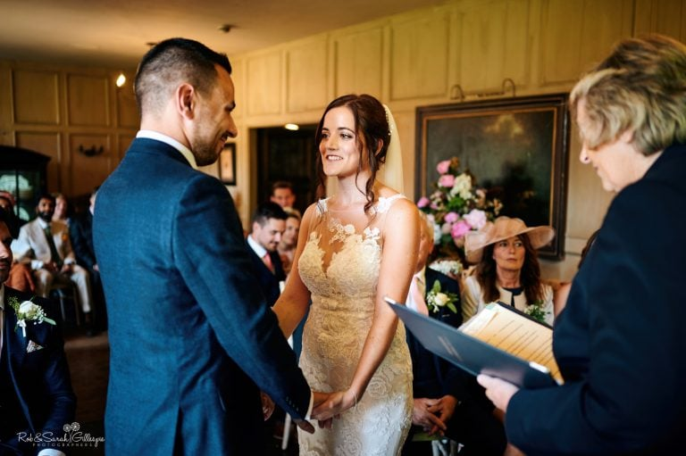 Bride and groom exchange wedding vows at Gorcott Hall