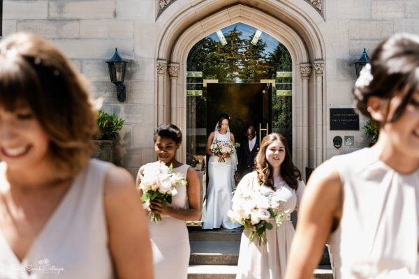 Bride and bridesmaids walk to wedding ceremony at Hampton Manor
