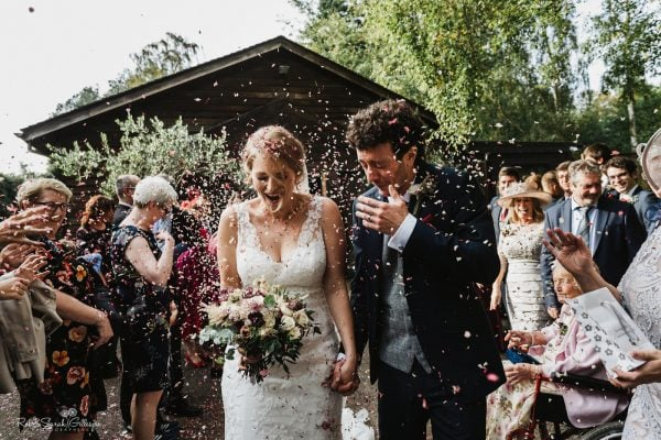 Bride and groom walk through confetti