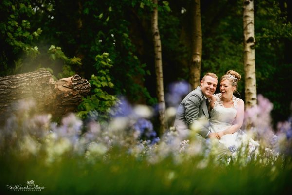 Bride and groom sitting on log in woods at Hampton Manor and laughing together
