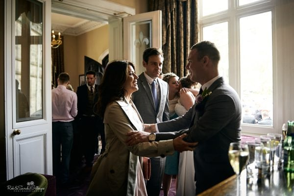 Groom greets wedding guests at Hampton Manor