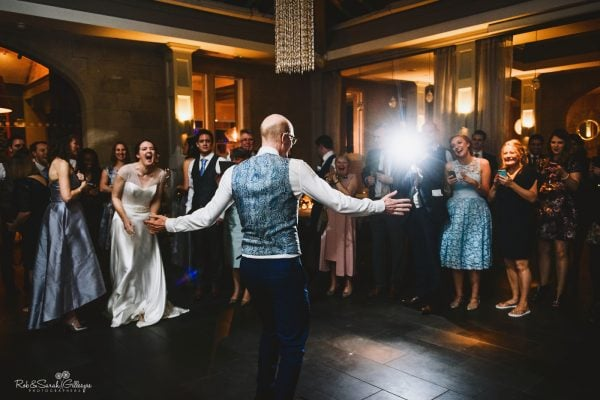 Groom on dancefloor cheered on by wedding guests