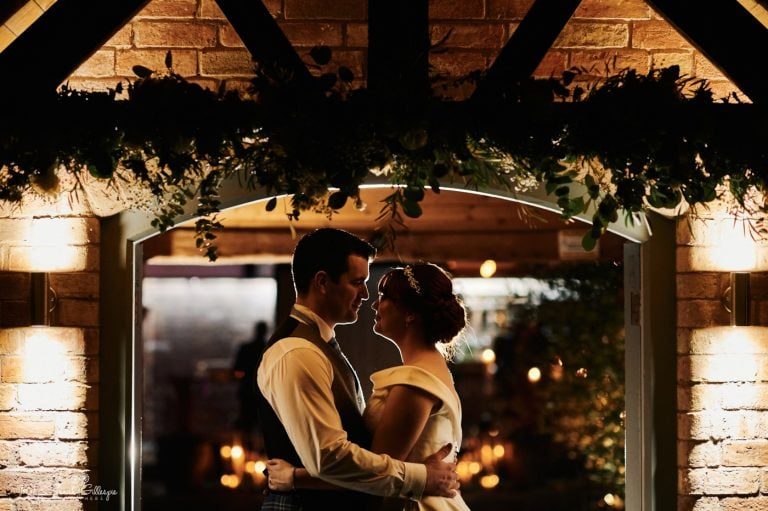 Bride and groom under courtyard doorway at night