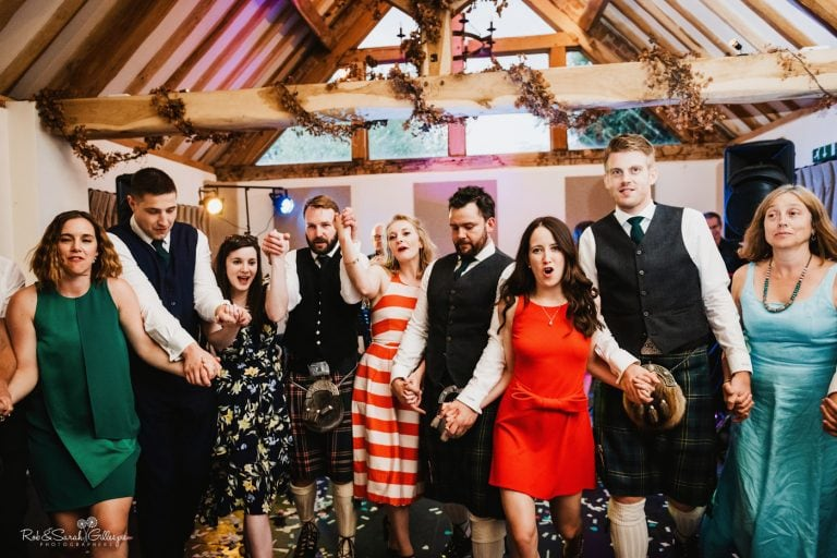 Wedding guests enjoy barn dance
