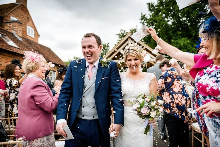 Bride and groom walk through confetti throw after wedding ceremony at Wethele Manor