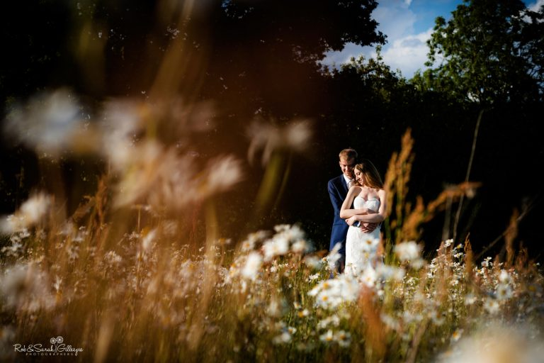Bride and groom relax and cuddle in wildflower field