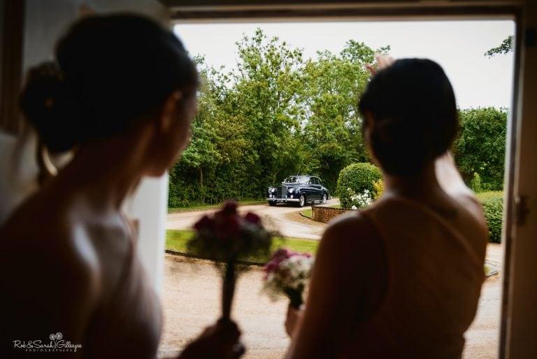 Bridesmaids watch as wedding car arrives