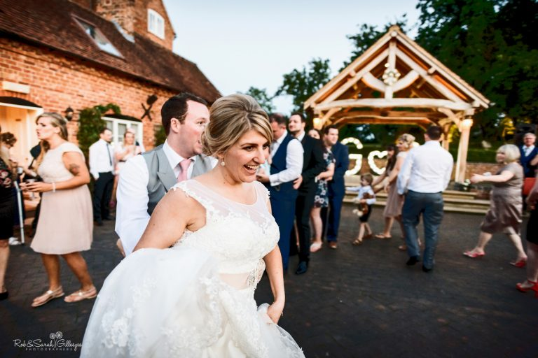 Bride, groom and wedding guests dance the conga in courtyard at Wethele Manor