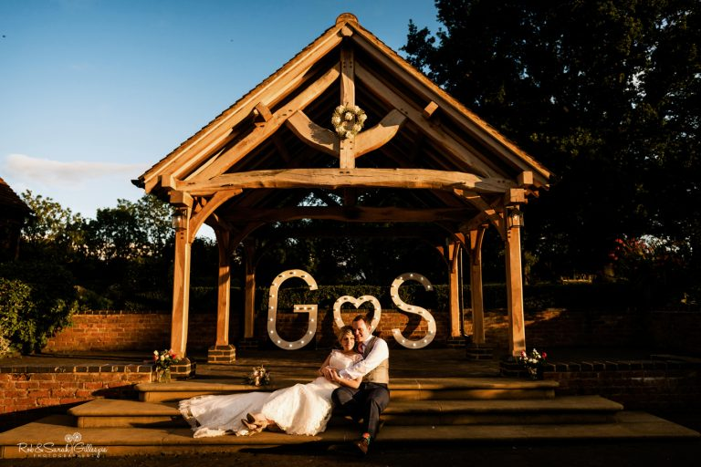 Bride and groom sit on step in front of wooden gazebo at Wethele Manor