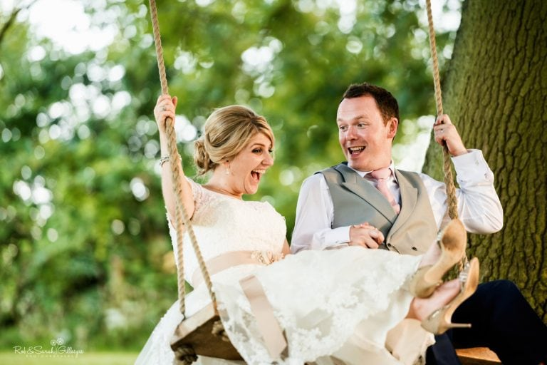 Bride and groom laughing on swing under tree in gardens at Wethele Manor