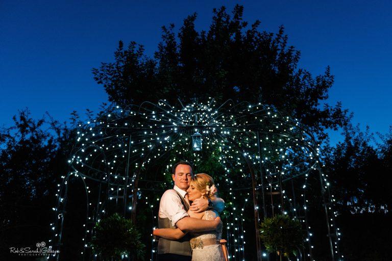 Bride and groom cuddle under illuminated gazebo at Wethele Manor
