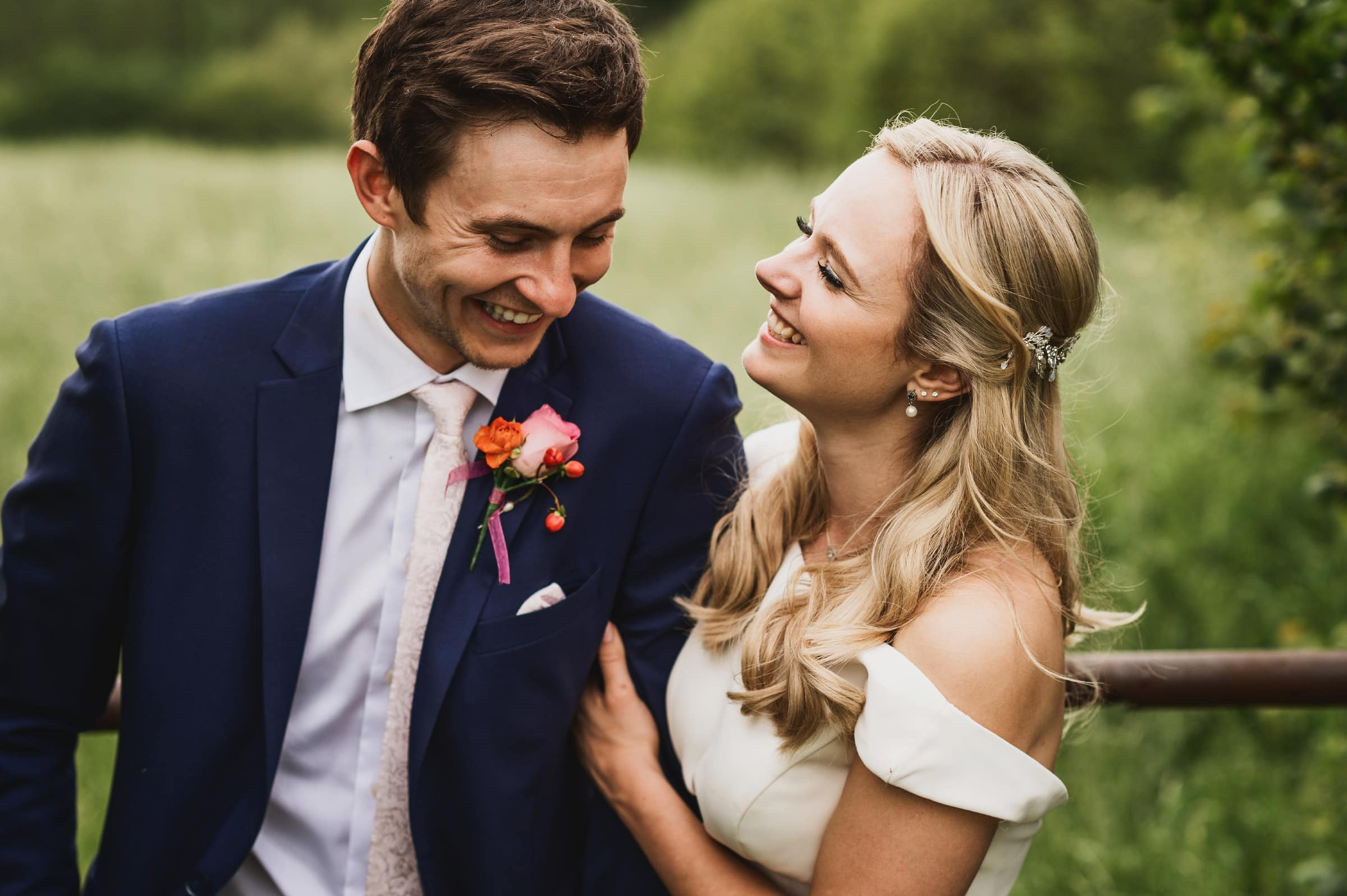 Newly married bride and groom laughing together in field