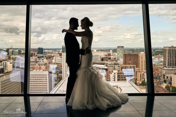 Bride and groom silhouetted against Birmingham city skyline