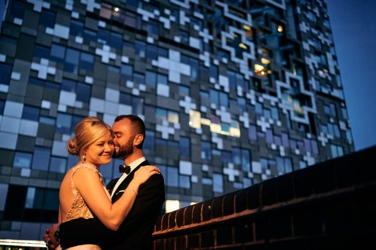 Newly married couple relax and cuddle in front of modern building at night