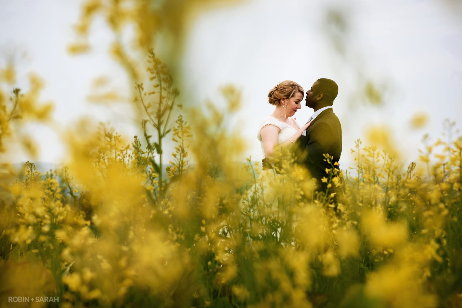 Bride and groom share a quiet moment in a beautiful yellow crop field