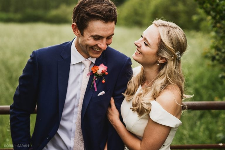Bride and groom laughing together in fields