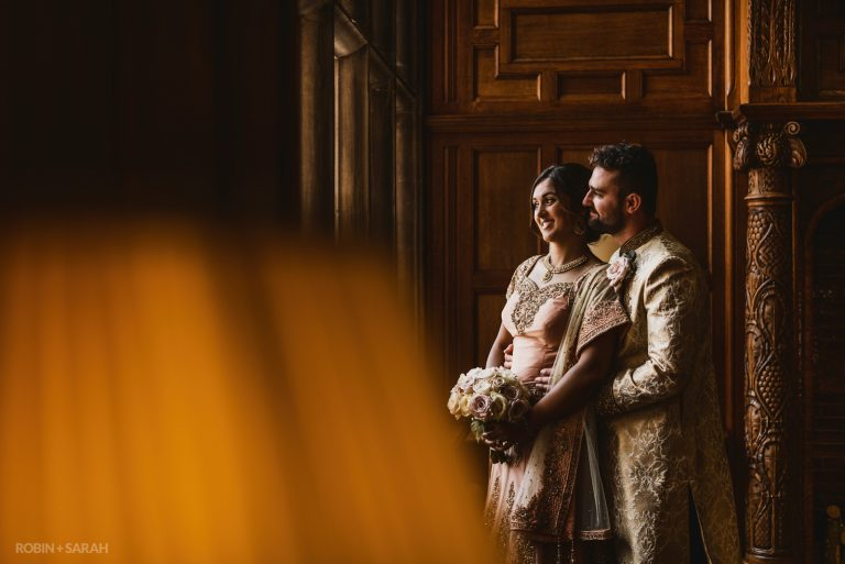 Couple in Indian wedding outfits cuddle in beautiful panelled room