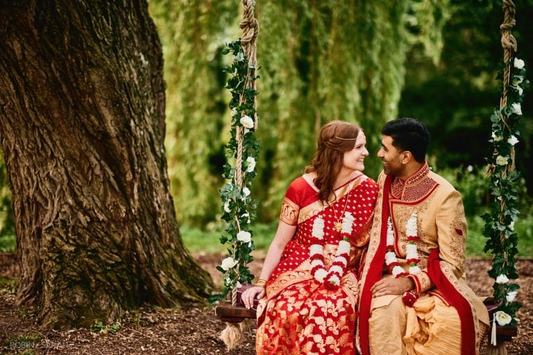 Bride and groom in Indian wedding outfits sitting on tree swing