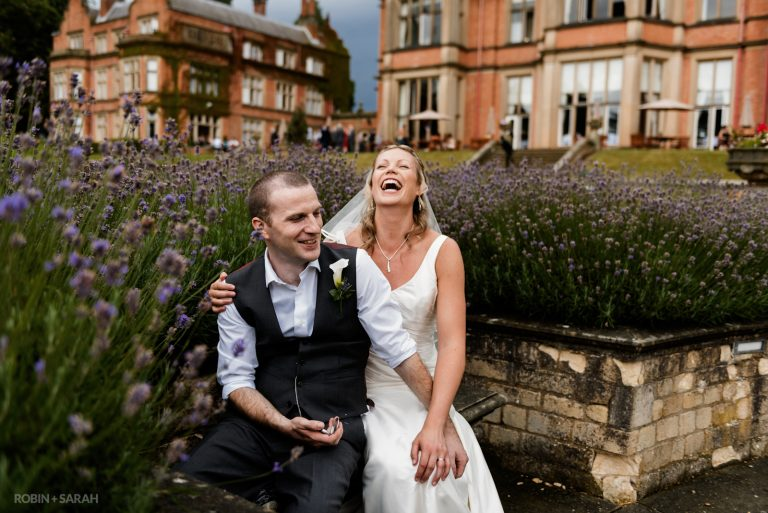 Bride and groom sitting in wedding venue grounds laughing together