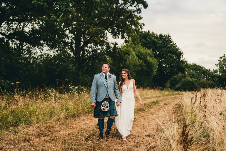 Bride and groom walking together through fields