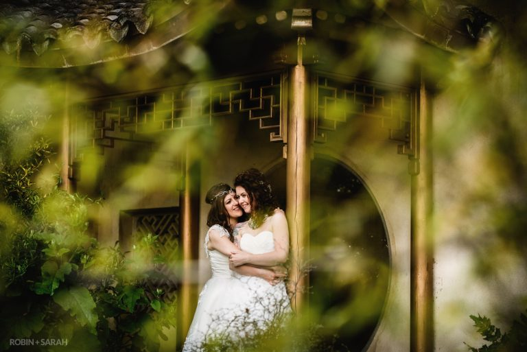 Two brides cuddle up in beautiful gardens