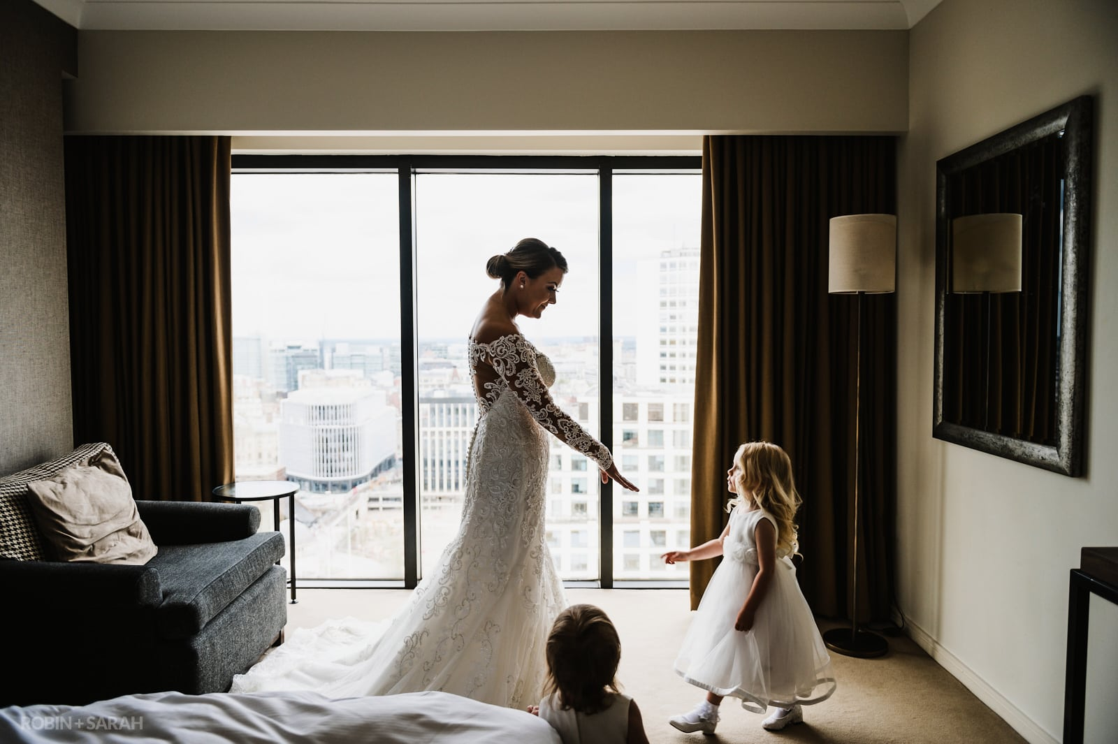 Bride holds hand out to young flowergirl as they prepare for wedding in hotel room