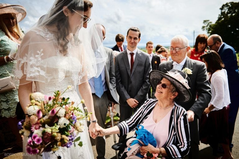Bride and grandmother hold hands after church wedding ceremony