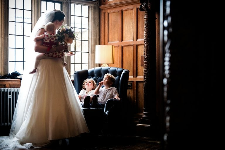 Bride stands holding baby as she talks to two young children seated in large chair