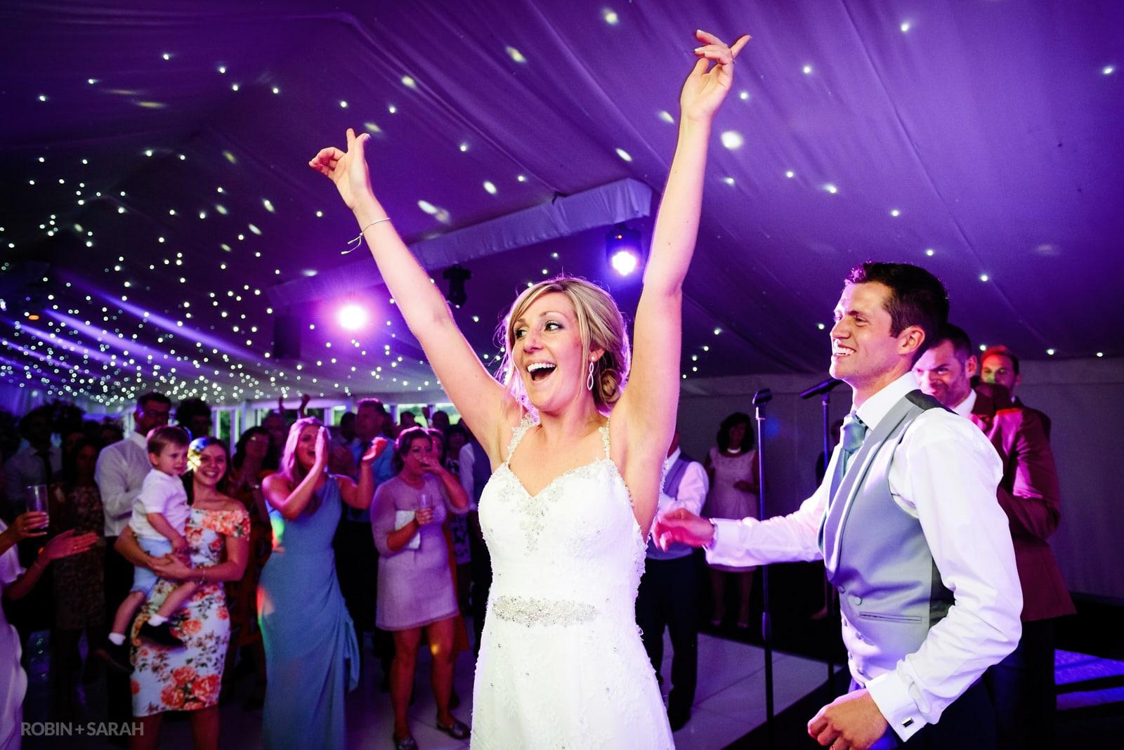 Bride raises her hands on dancefloor as guests watch and laugh