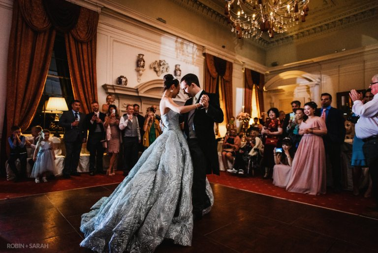 Bride and groom perform first dance as guests watch and clap