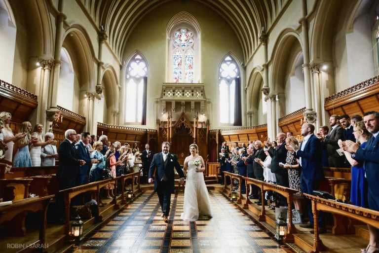 Bride and groom walk out of wedding ceremony in beautiful hall as guests clap