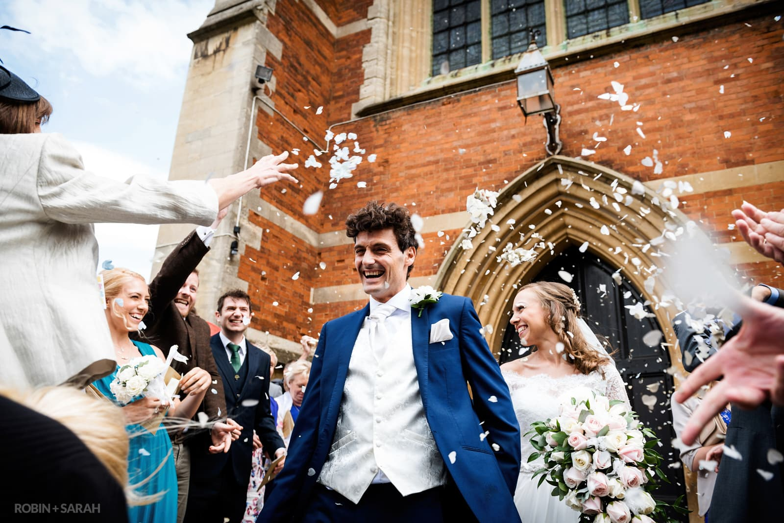 Bride and groom walk through confetti thrown by guests outside church