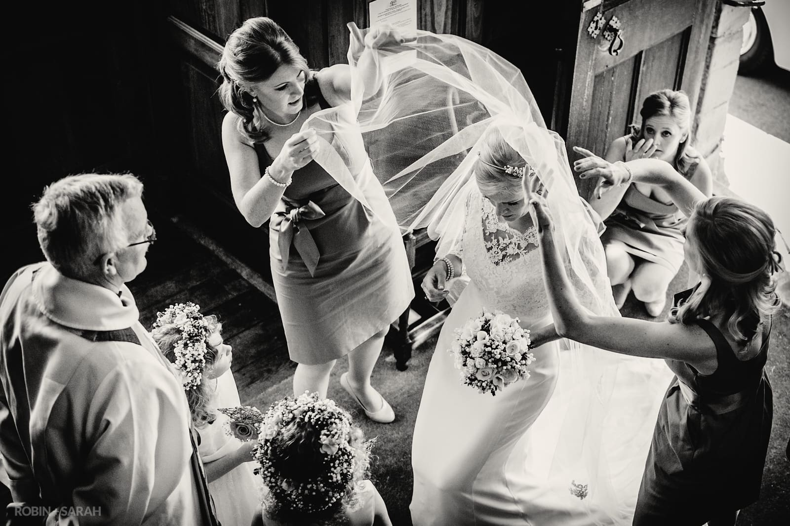 Bride has veil lifted over her head by bridesmaids before church wedding service