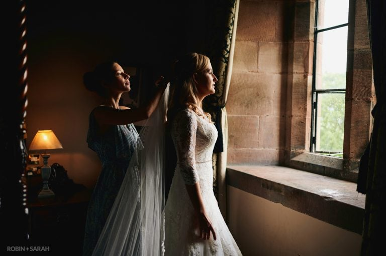 Bride in beautiful window light as she has veil fitted