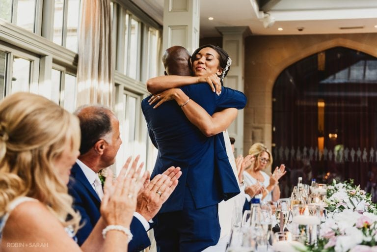 Bride hugs dad during wedding speeches as guests clap