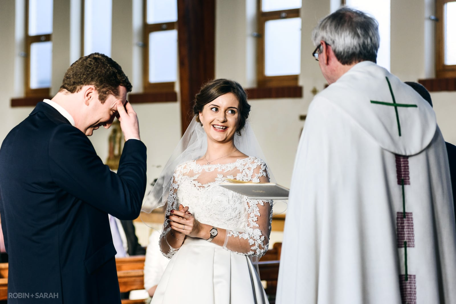 Bride laughing as groom makes mistake during wedding vows in church