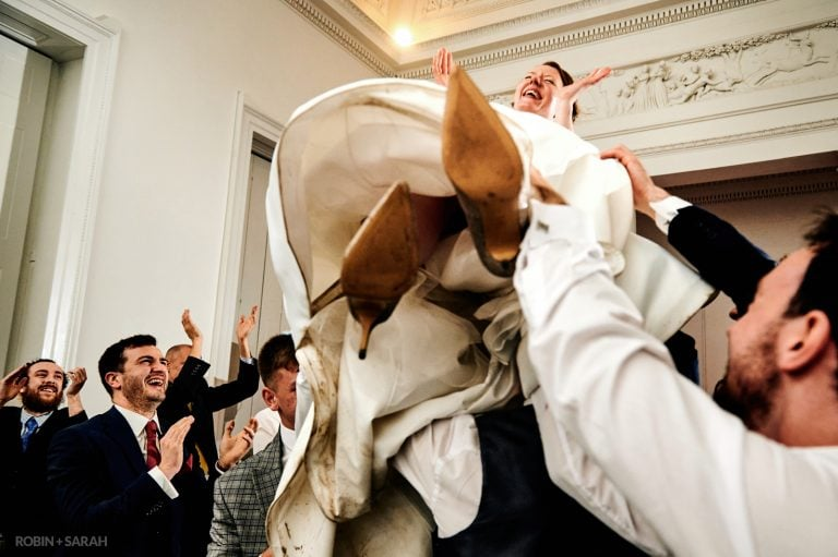 Bride laughing has guests lift her up off dancefloor during wedding party