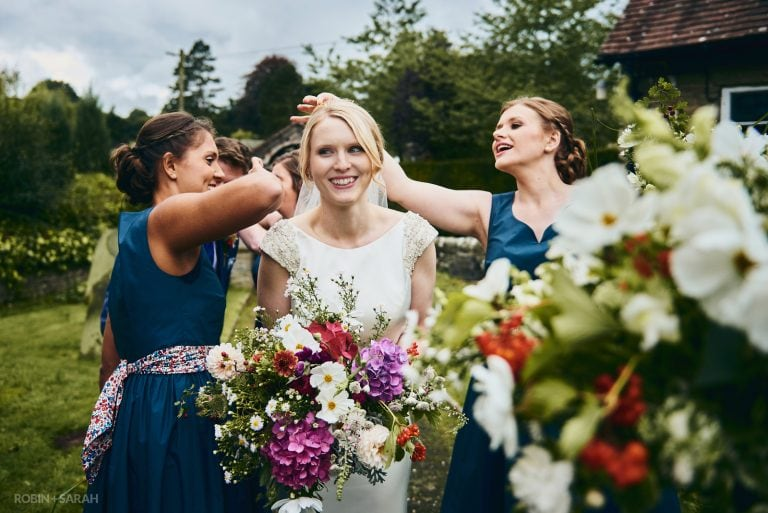 Bride laughs as her friends pick confetti out of her hair