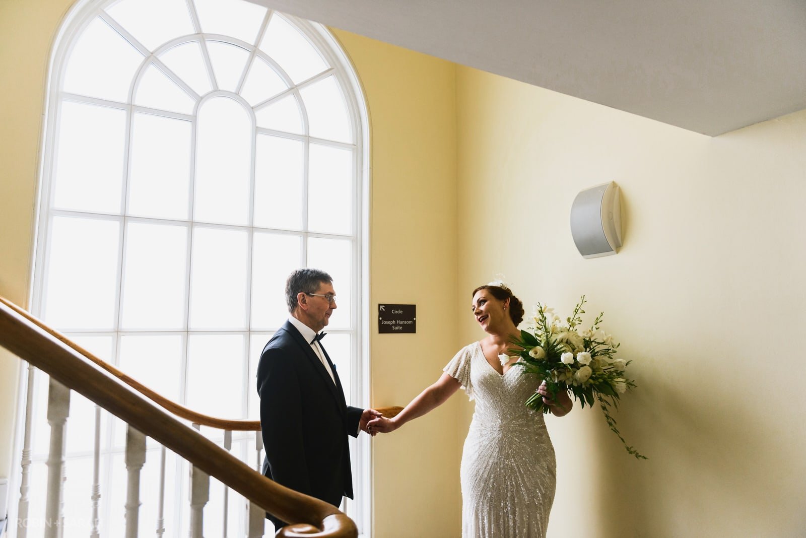Dad sees his daughter ijn wedding dress for the first time in front of beautiful arched window