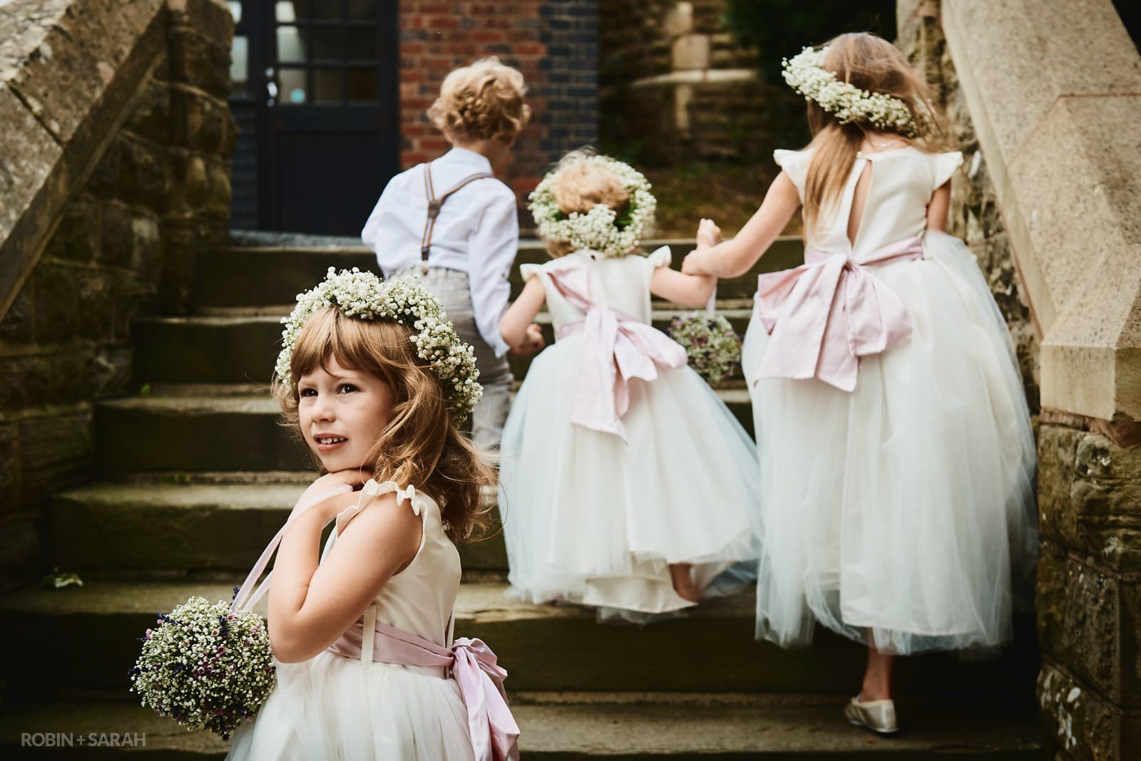 Flower girl pauses on steps before church wedding ceremony