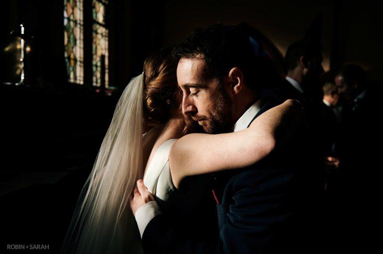 Bride hugs friend after wedding with beautiful light