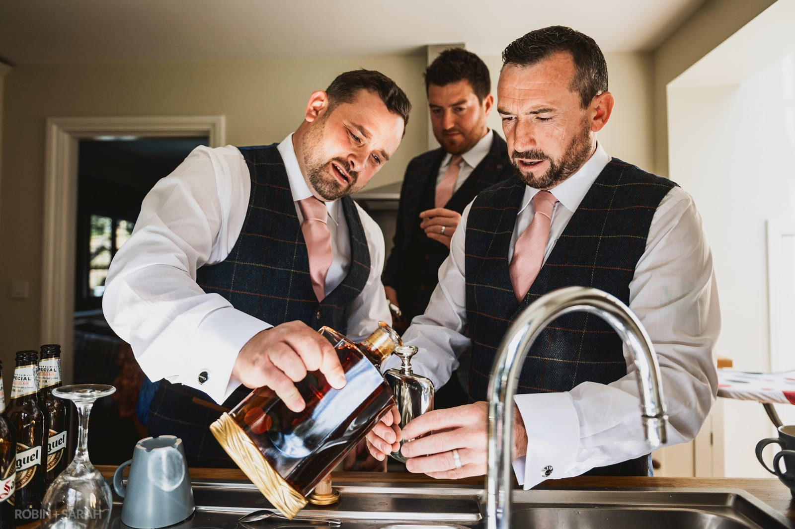 Groom and friends pour brandy before wedding